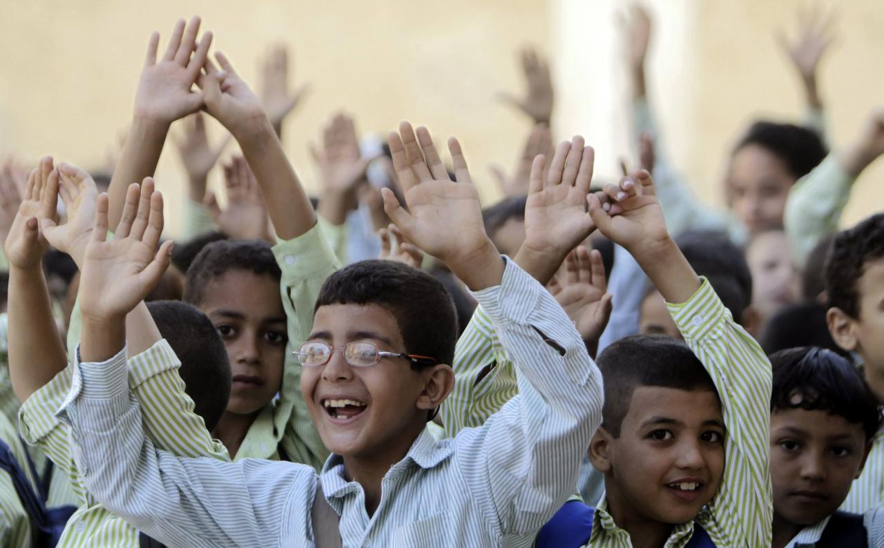 Students line up and raise their hands on the first day of their new school year at a government school in Giza, south of Cairo September 22, 2013. Students resumed their studies at the beginning of the new academic year this weekend amid parental concerns of a possible lack of security after the summer vacation ends. REUTERS/Mohamed Abd El Ghany (EGYPT - Tags: POLITICS EDUCATION)
