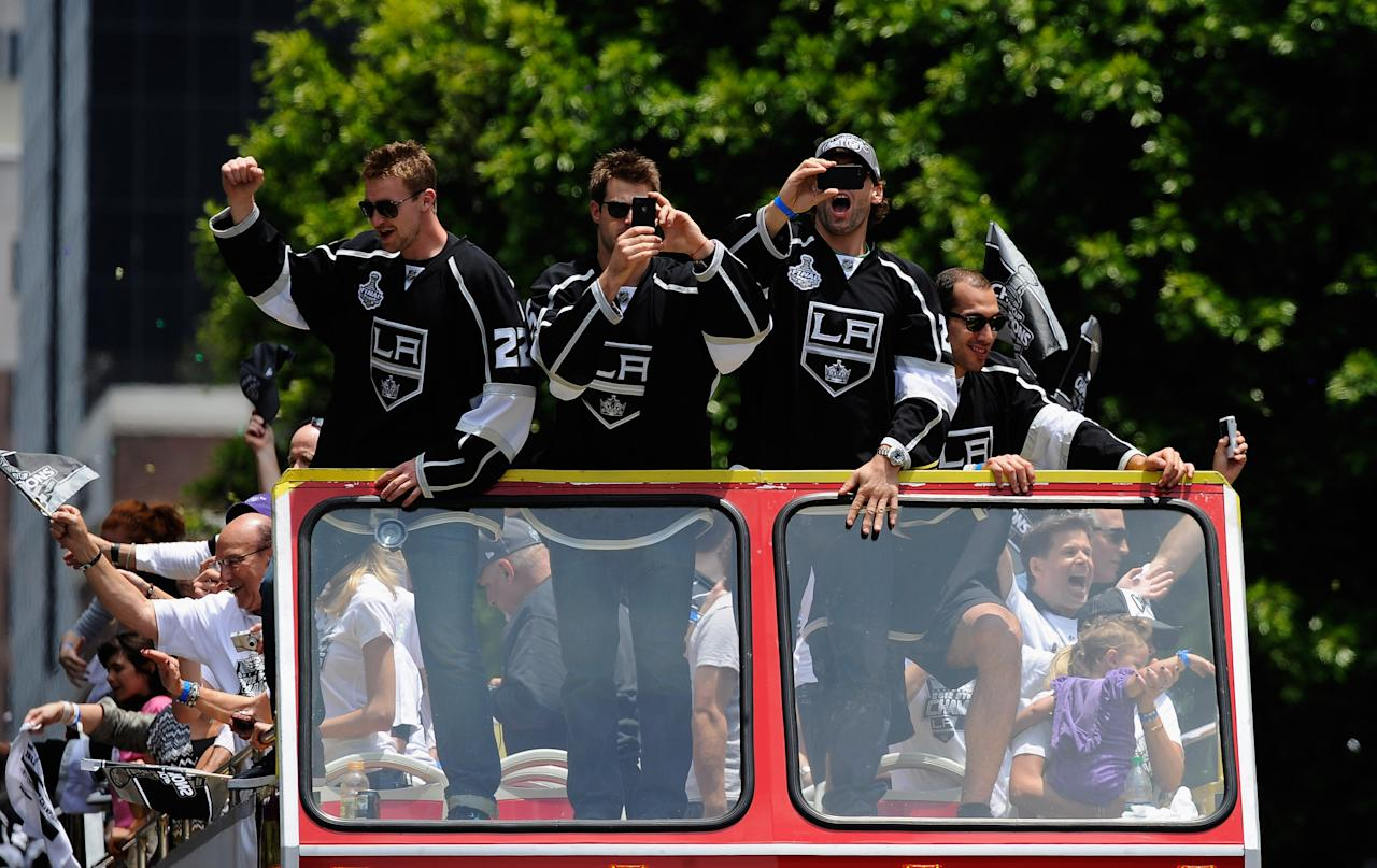 LOS ANGELES, CA - JUNE 14:  Los Angeles Kings team members from  left Trevor Lewis #22, Brad Richardson #15 and Jarret Stoll #28 wave to cheering fans during the Stanley Cup victory parade on June 14, 2012 in Los Angeles, California. The Kings are celebrating their first NHL Championship in the team's 45-year-old franchise history.  (Photo by Kevork Djansezian/Getty Images)