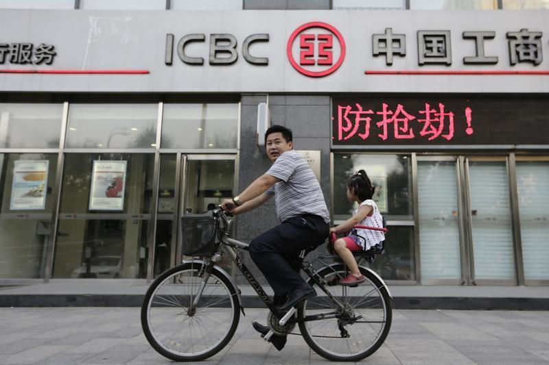 A man and his daughter ride a bicycle past a branch of the Industrial and Commercial Bank of China in Beijing