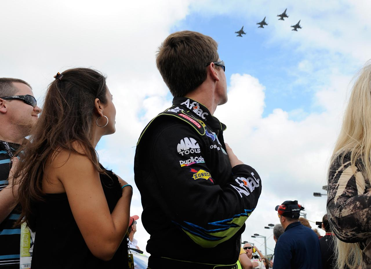 HOMESTEAD, FL - NOVEMBER 20:  Carl Edwards, driver of the #99 Aflac Ford, and wife Kate Edwards watch a fly over during the singing of the national anthem as they stand next to his car on the grid before the NASCAR Sprint Cup Series Ford 400 at Homestead-Miami Speedway on November 20, 2011 in Homestead, Florida.  (Photo by Jared C. Tilton/Getty Images)