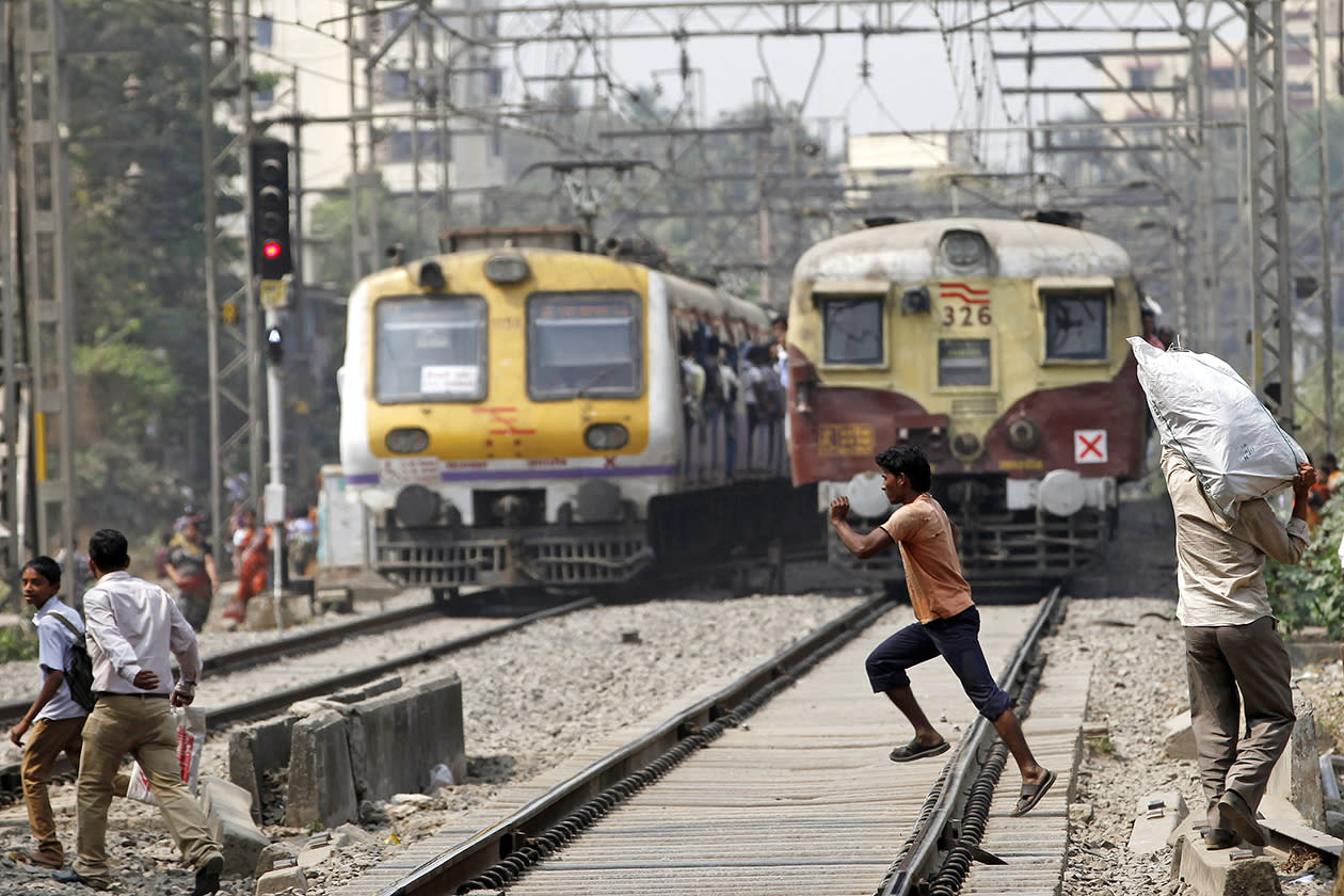 An Indian boy runs across a rail track in front of a running train in Mumbai, India.