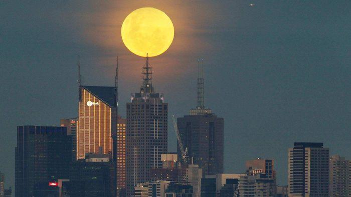 The supermoon, here rising over Melbourne, has generated high tides which have eroded up to 2.5 meters of beaches on the Gold Coast