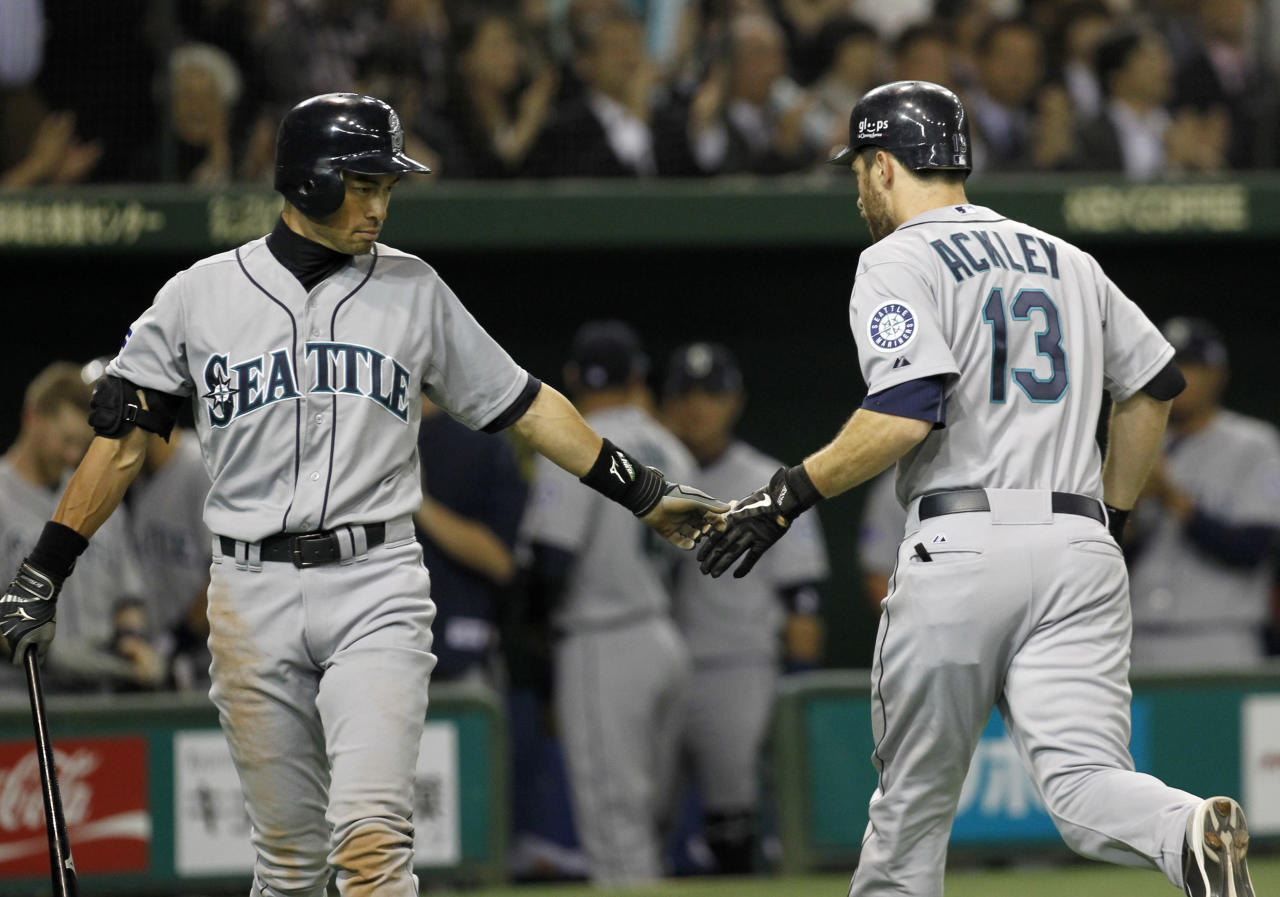 Seattle Mariners' Dustin Ackley (13) is congratulated by teammate Ichiro Suzuki at home after hitting a solo shot against Oakland Athletics starter Brandon McCarthy in the fourth inning of their American League season opening MLB baseball game at Tokyo Dome in Tokyo, Wednesday, March 28, 2012. in Tokyo, Wednesday, March 28, 2012. (AP Photo/Koji Sasahara)