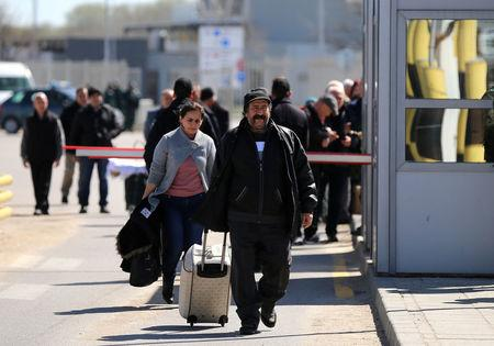 People carry their luggage as they cross the border crossing between Turkey and Bulgaria on foot during a protest at Kapitan Andreevo border checkpoint, Bulgaria March 24, 2017. Supporters of Bulgarian nationalist parties blocked the crossing in order to prevent ethnic Turkish citizens with Bulgarian passports to vote in the Sunday parliamentary elections. REUTERS/Stoyan Nenov