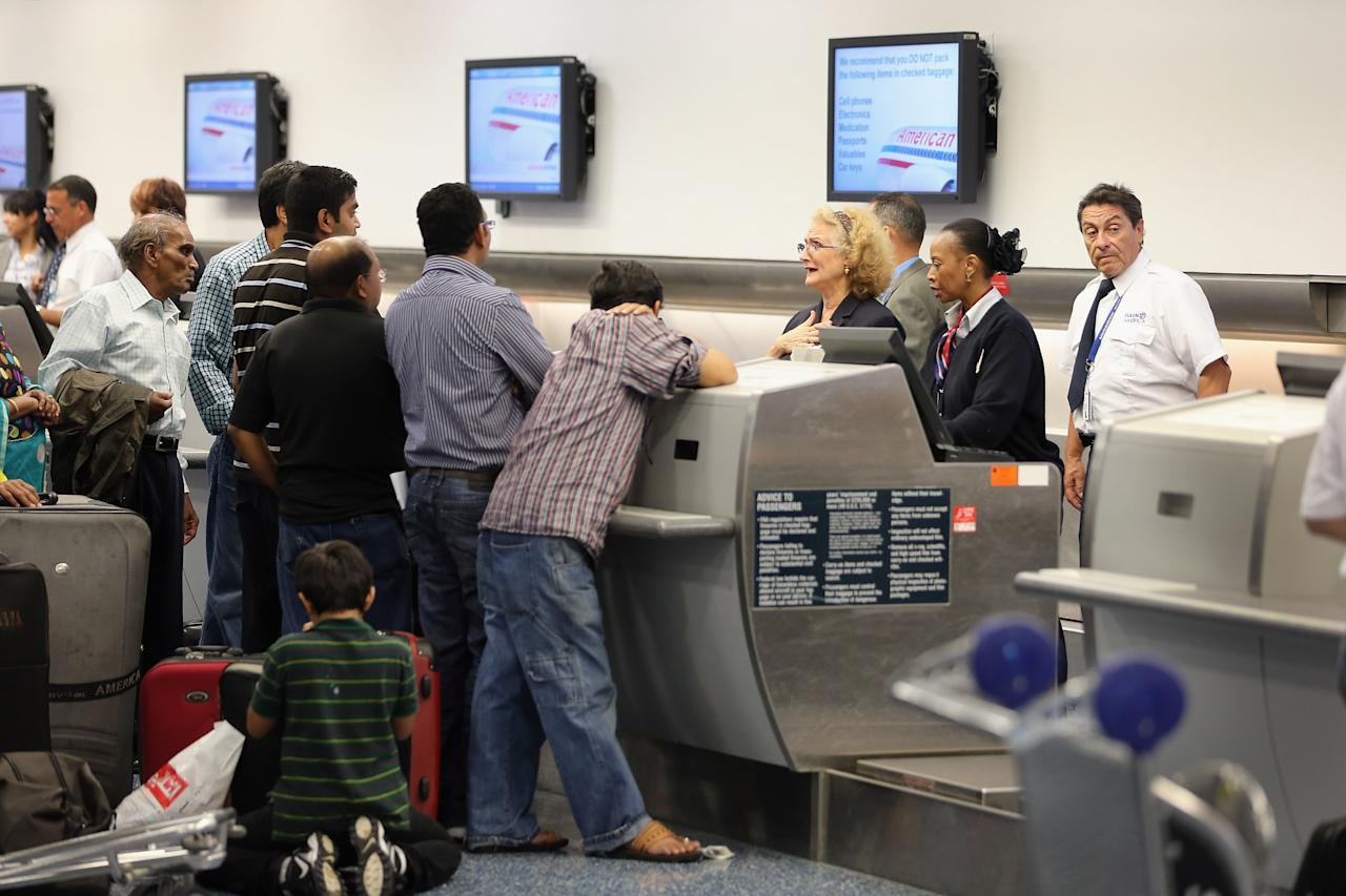 MIAMI, FL - APRIL 16:  American Airlines passenger are helped at the ticket counter at Miami International Airport on April 16, 2013 in Miami, Florida. Thousands of American Airlines travelers became stranded today when the airline was forced to ground all its flights after a nationwide problem with its computer systems  (Photo by Joe Raedle/Getty Images)