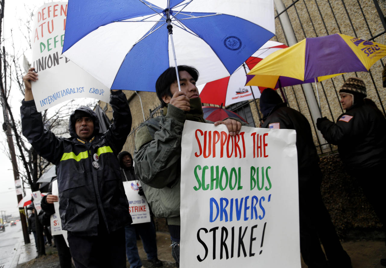 Bus drivers and supporters walk a picket line in front of a bus depot in New York, Wednesday, Jan. 16, 2013. More than 8,000 New York City school bus drivers and matrons went on strike over job protection Wednesday morning, leaving some 152,000 students, many disabled, trying to find other ways to get to school. (AP Photo/Seth Wenig)