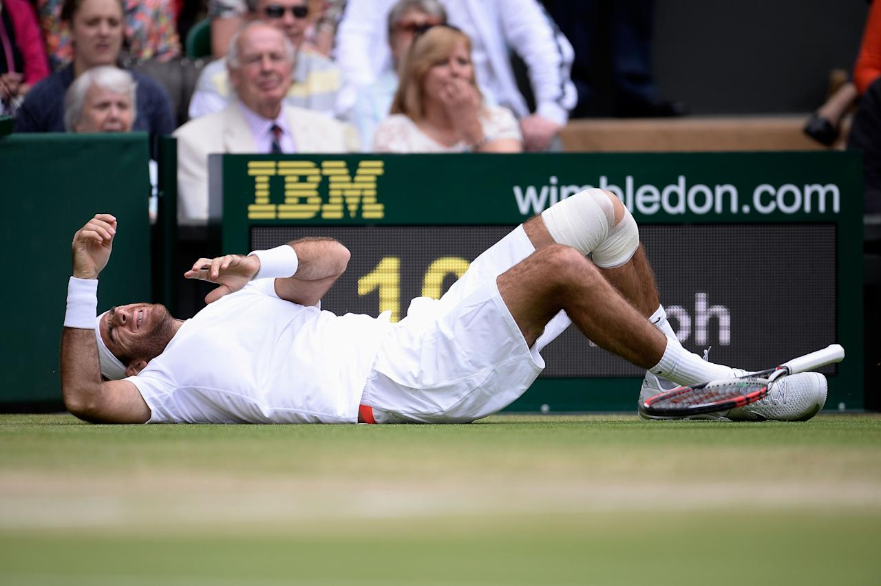 LONDON, ENGLAND - JULY 03: Juan Martin Del Potro of Argentina grimaces after slipping on the grass during the Gentlemen's Singles quarter-final match against David Ferrer of Spain on day nine of the Wimbledon Lawn Tennis Championships at the All England Lawn Tennis and Croquet Club at Wimbledon on July 3, 2013 in London, England. (Photo by Dennis Grombkowski/Getty Images)