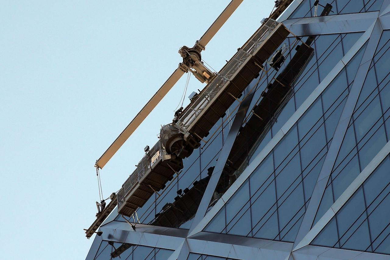 NEW YORK, NY - JUNE 12: Broken scaffolding on top of the 46-story Hearst Tower building is viewed after two trapped window washers were rescued on June 12, 2013 in New York City. The workers, who were servicing the window-washing equipment when the scaffolding broke, were left dangling 500 feet above Eighth Avenue. Firefighters and NYPD emergency service unit officers were were able to rescue the men as hundreds of onlookers gazed up from the street. (Photo by Spencer Platt/Getty Images)