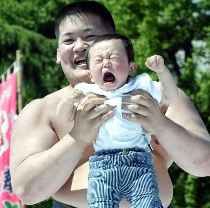 TOKYO, JAPAN: APRIL 29   A baby cries as a university sumo club members holds them during Crying-Sumo at Sensoji Temple April 29, 2004 in Tokyo, Japan. The baby that cries first wins the game. The ceremony has been taking place in Japan to wish for the good health of the child as it is said that crying is good for the health of babies. Majority of the children who participate are less than 1 year old. (Photo by Koichi Kamoshida/Getty Images)