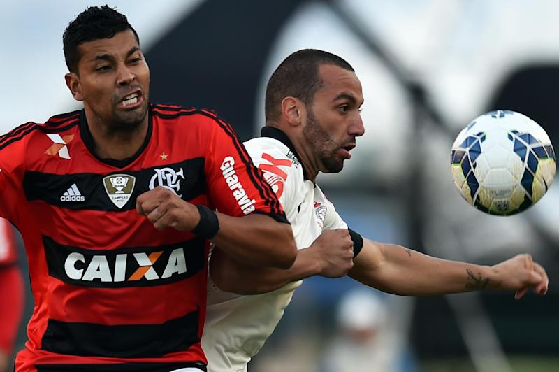 Guilherme (R) of Corinthians vies for the ball with Andre Santos (L) of Flamengo during their Brazilian championship football match at Pacaembu stadium in Sao Paulo, Brazil on April 27, 2014