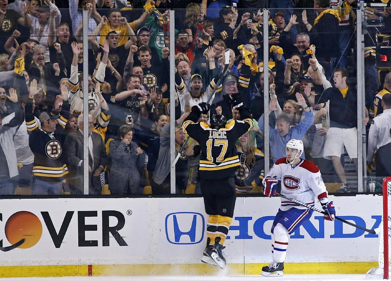 Boston Bruins left wing Milan Lucic (17) celebrates his goal with fans as Montreal Canadiens defenseman Alexei Emelin (74) skates away during the third period in Game 2 of an NHL hockey second-round playoff series in Boston, Saturday, May 3, 2014. The Bruins won 5-3. (AP Photo/Elise Amendola)
