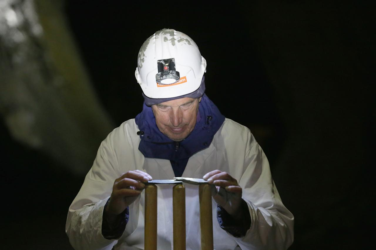 KESWICK, ENGLAND - DECEMBER 05:  Umpire Norman Shuttleworth places slate bales on the stumps ready for village teams Threlkeld and Caldbeck to take part in the world's first underground cricket match inside Honister Slate Mine on December 5, 2013 in Keswick, England. The Christmas fixture took part 600m (2,000ft) inside Fleetwith Pike at  Englands last working slate mine at Honister in the Lake District. The game is one of many unusual venues the teams have played in to raise money to fix Threlkeld Cricket Club's flood damaged ground. The match was won by Caldbeck Village.  (Photo by Christopher Furlong/Getty Images)