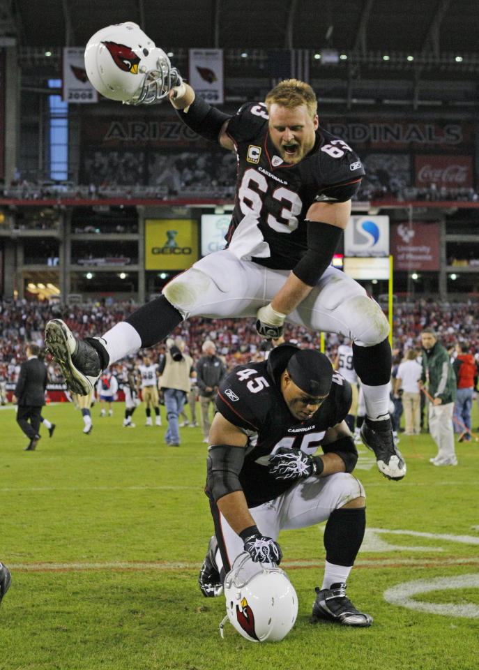 Arizona Cardinals' Lyle Sendlein leaps over a praying Reagan Maui'a after Patrick Peterson returned a punt 99 yards for a touchdown to beat the St. Louis Rams in overtime in an NFL football game Sunday, Nov. 6, 2011, in Glendale, Ariz. The Cardinals won 19-13. (AP Photo/The Arizona Republic, David Kadlubowski) MARICOPA COUNTY OUT NO SALES