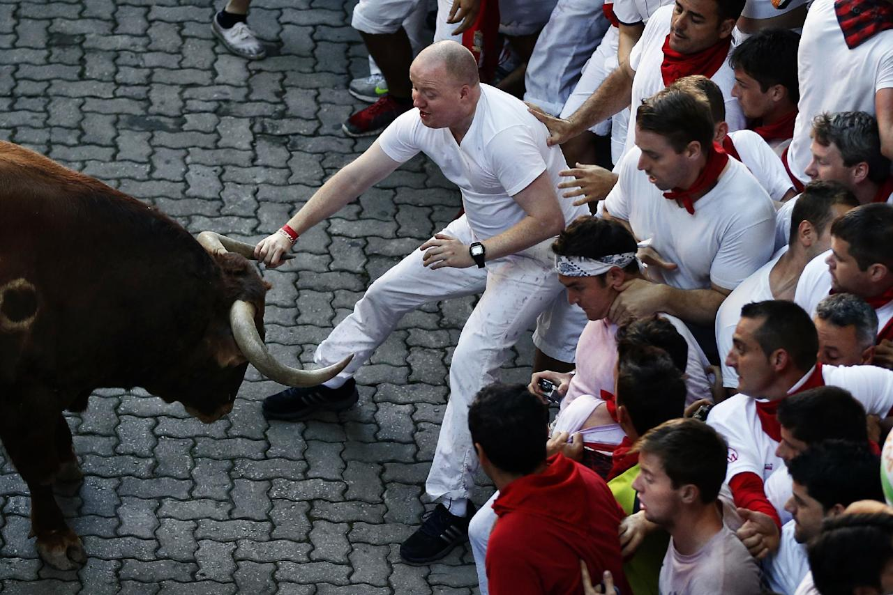 "A reveler grabs the horn of an Alcurrucen's ranch fighting bull during the running of the bulls of the San Fermin festival, in Pamplona, Spain, Sunday, July 7, 2013. Revelers from around the world arrive to Pamplona every year to take part on some of the eight days of the running of the bulls glorified by Ernest Hemingway's 1926 novel ""The Sun Also Rises."" (AP Photo/Daniel Ochoa de Olza)"