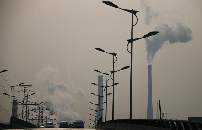 Smoke rises from chimneys of a steel plant next to a viaduct on a hazy day in Tangshan