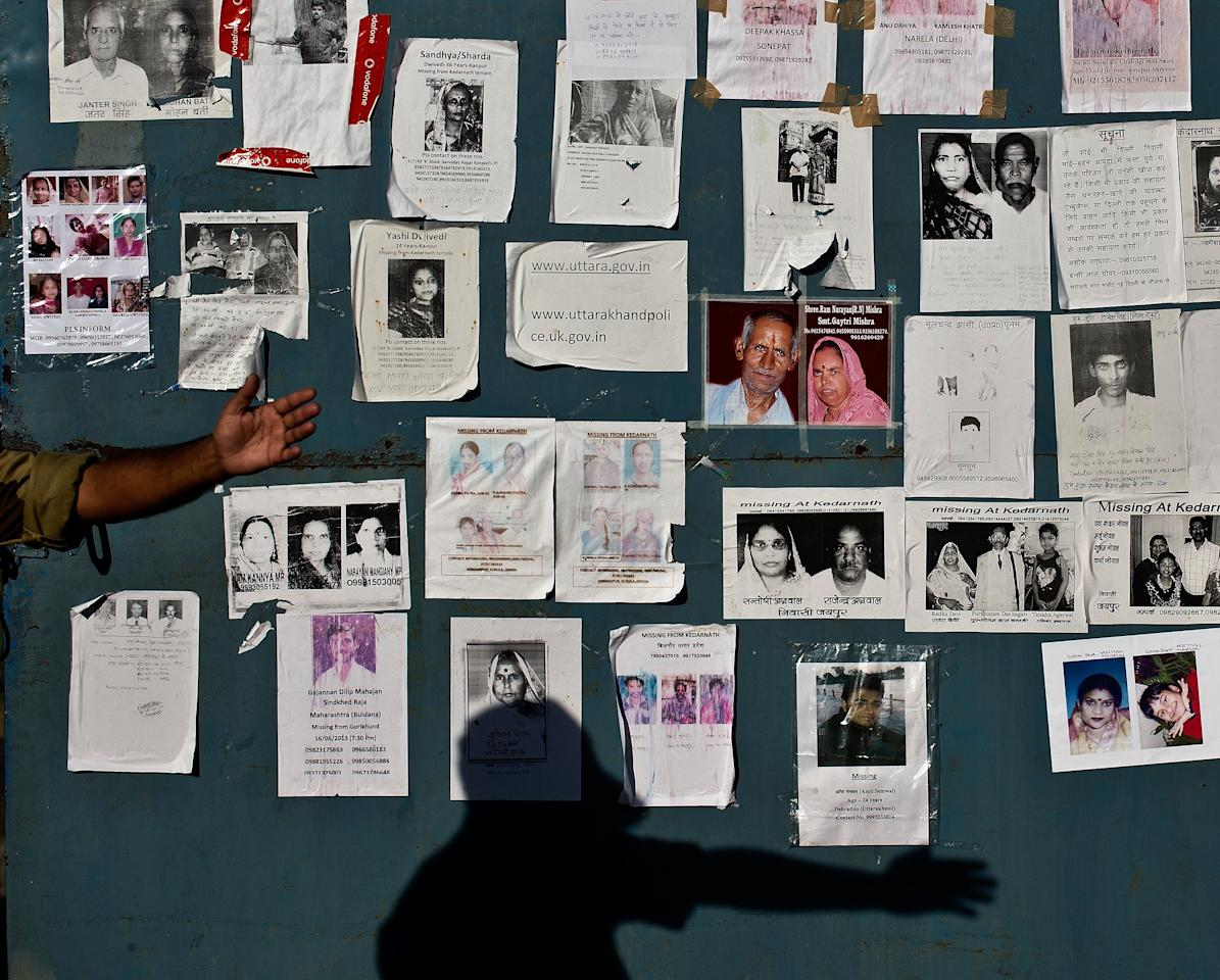 An Indian security official gestures to clear the road in front of portraits of missing pilgrims pasted on the gates of the Jolly Grant Airport in Dehradun, state capital of Uttarakhand, on June 26, 2013. Around 1,000 people have been killed in flash floods and landslides in northern India, as a top official warned June 24 that rebuilding of the devastated Himalayan region would take years.  AFP PHOTO/MANAN VATSYAYANA
