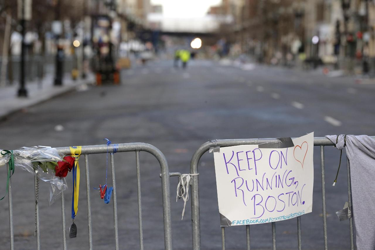 A sign hangs from a barricade on Boylston Street near the finish line of the Boston Marathon, Wednesday, April 17, 2013, in Boston. The city continues to cope following Monday's explosions near the finish line of the marathon. (AP Photo/Julio Cortez)