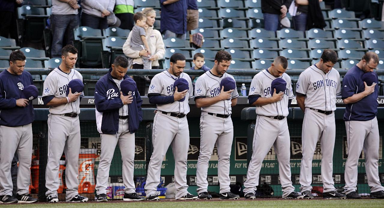San Diego Padres players stand during a moment of silence in honor of Tony Gwynn before a baseball game against the Seattle Mariners Monday, June 16, 2014, in Seattle. It was announced earlier Monday that Gwynn, who had more than 3,100 hits during a career spanning two decades, died at age 54 following a battle with oral cancer. (AP Photo/Elaine Thompson)