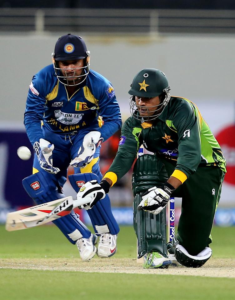 DUBAI, UNITED ARAB EMIRATES - DECEMBER 11:  Sharjeel Kan of Pakistan bats as Kumar Sangakkara of Sri Lanka looks on during the first Twenty20 International match between Pakistan and Sri Lanka at Dubai Sports City Cricket Stadium on December 11, 2013 in Dubai, United Arab Emirates.  (Photo by Francois Nel/Getty Images)
