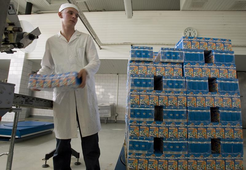 A worker loads a packs of milk at a milk plant in Minsk