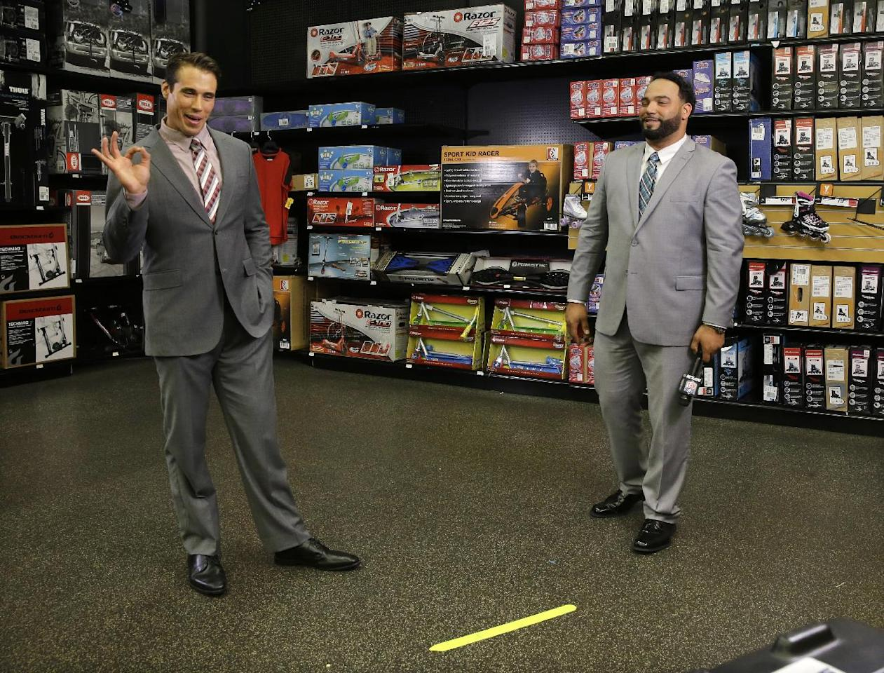 In this photo taken on Wednesday, June 18, 2014, former first-round draft pick, quarterback Brady Quinn, left, signals that he and fellow NFL football player, defensive tackle Antonio Garay, right, did well in a practice interview at a sporting goods store during the NFL's Broadcast Boot Camp in Mount Laurel, N.J. Twenty-five current and former players participating in the NFL's Broadcast Boot Camp this week, are vying for broadcasting gigs. (AP Photo/Mel Evans)