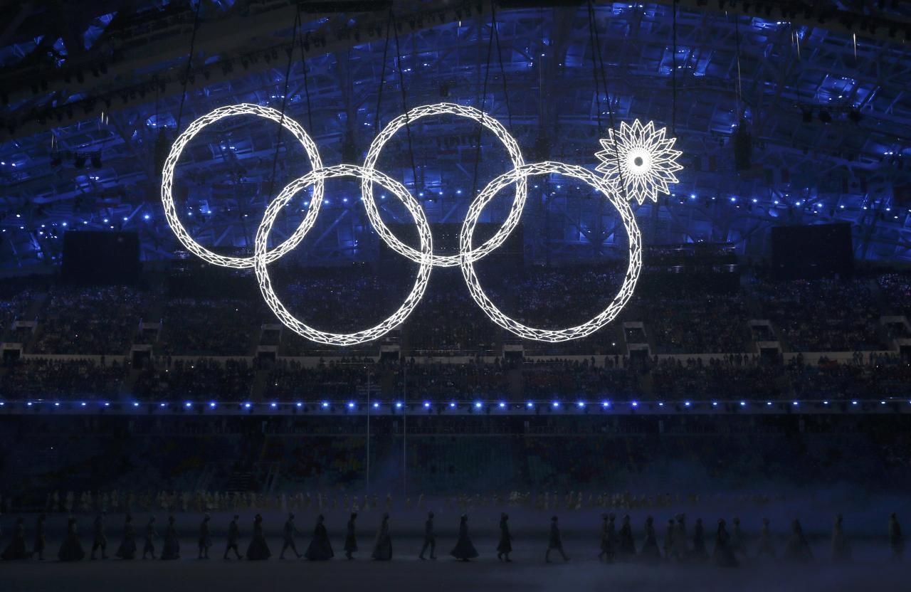 Participants march by as one of the Olympic Rings fails to completely illuminate during the opening ceremony  of the 2014 Sochi Winter Olympics, February 7, 2014. REUTERS/Phil Noble (RUSSIA - Tags: OLYMPICS SPORT)