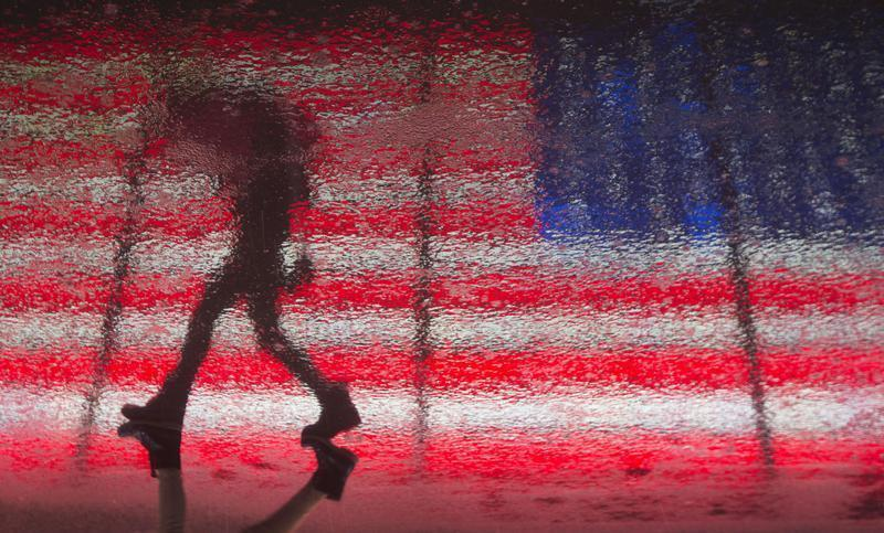 A woman is reflected in the wet pavement as she walks past a U.S. flag billboard in Times Square during a rare winter thunderstorm in New York
