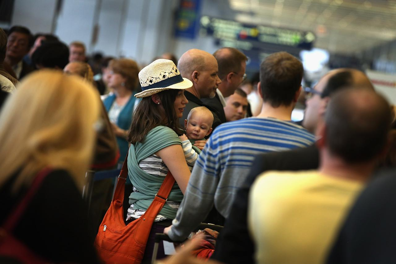 CHICAGO, IL - APRIL 16:  American Airlines passengers Chelsea Hunt and her six-month-old baby Lucas wait in line to reschedule a flight to Dallas at O'Hare Airport on April 16, 2013 in Chicago, Illinois.  Thousands of American Airlines travelers became stranded today when the airline was forced to ground all its flights after a nationwide problem with its computer systems.  (Photo by Scott Olson/Getty Images)