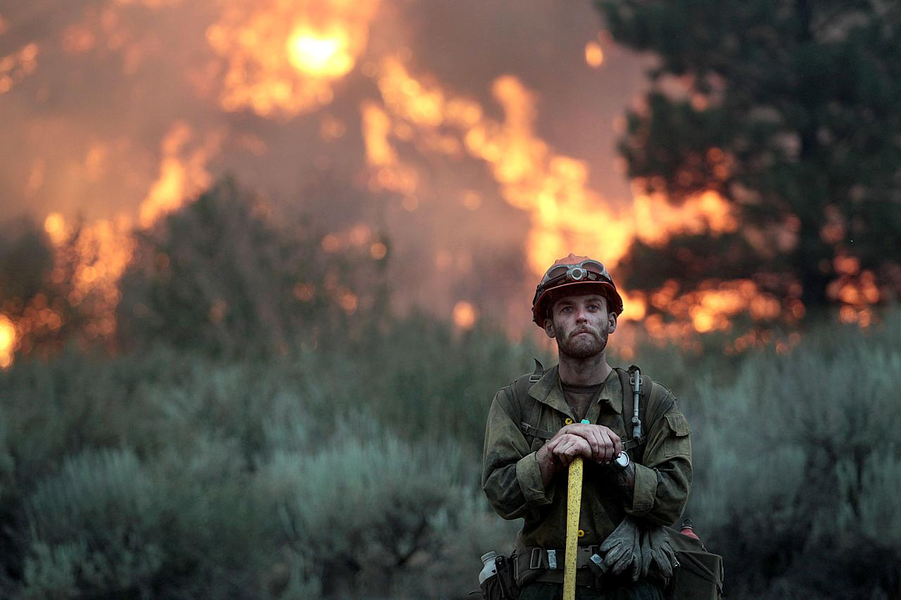 In this Monday, Aug. 12, 2013 photo, a firefighter with the Idaho City Hotshots looks for spot fires during a back burn along the Pine-Featherville Road while battling the more than 90,000-acre Elk Fire Complex near Pine, Idaho. Fire crews in central Idaho capitalized on favorable winds Tuesday to continue burnout operations around a small mountain community, seeking to push a wildfire toward an area torched by a massive blaze last year. (AP Photo/The Times-News, Ashley Smith) MANDATORY CREDIT