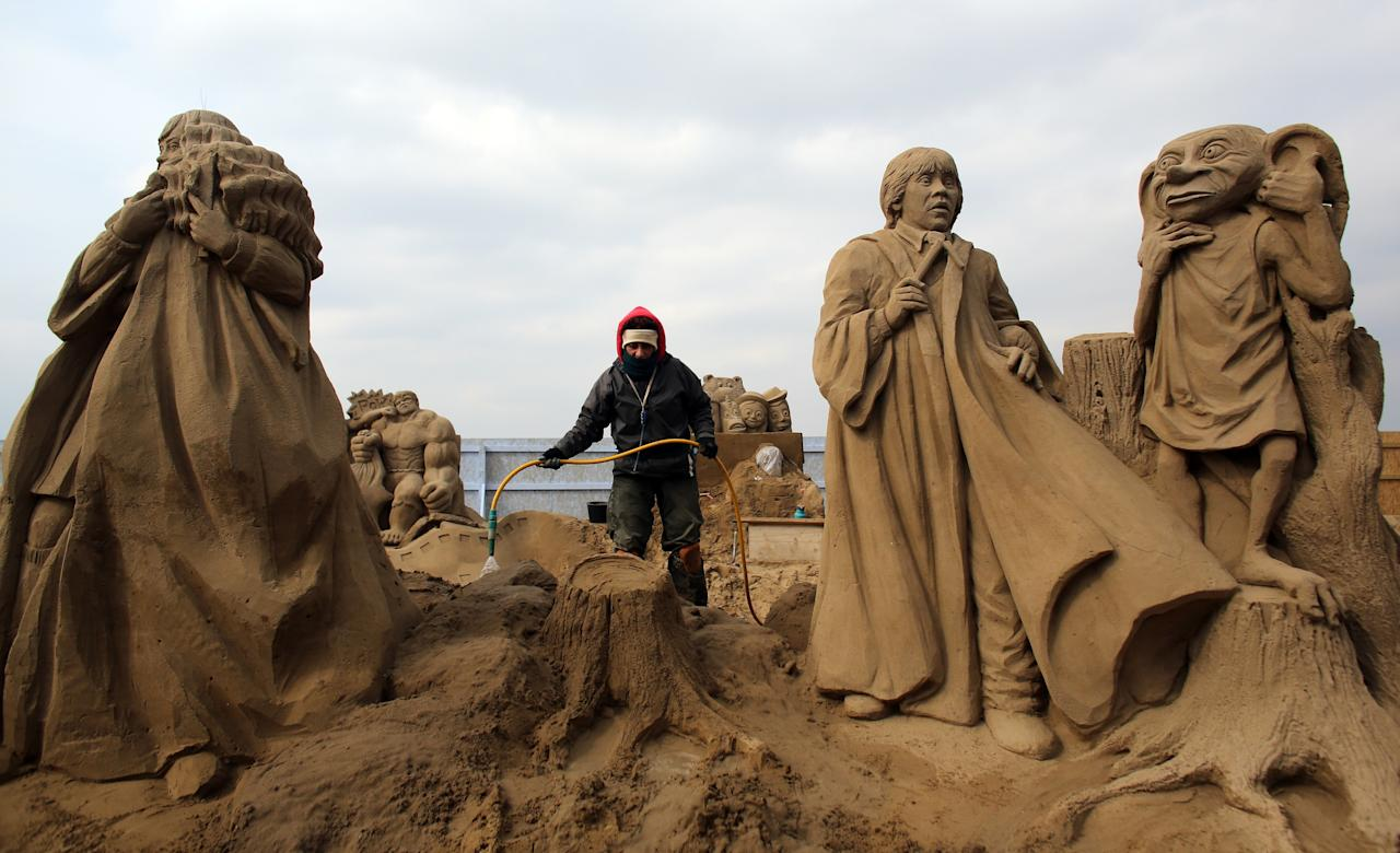 WESTON-SUPER-MARE, ENGLAND - MARCH 26:  A sand sculptor works on a Harry Potter themed sand sculpture as pieces are prepared as part of this year's Hollywood themed annual Weston-super-Mare Sand Sculpture festival on March 26, 2013 in Weston-Super-Mare, England. Due to open on Good Friday, currently twenty award winning sand sculptors from across the globe are working to create sand sculptures including Harry Potter, Marilyn Monroe and characters from the Star Wars films as part of the town's very own movie themed festival on the beach.  (Photo by Matt Cardy/Getty Images)
