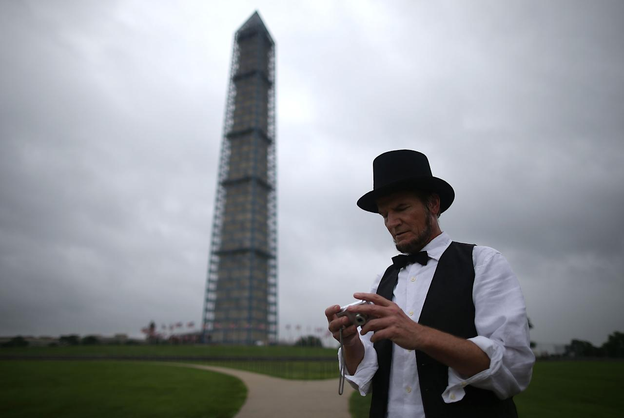 WASHINGTON, DC - JULY 03: Abraham Lincoln imperonator Johnny Schuler looks at his camera while attending a toy gun during a rally on the grounds of the Washington Monument July 3, 2013 in Washington, DC. Gun rights advocates participates in the Armed Toy Gun March on D.C. to raise money and toys for the Toys for Tots program. (Photo by Mark Wilson/Getty Images)
