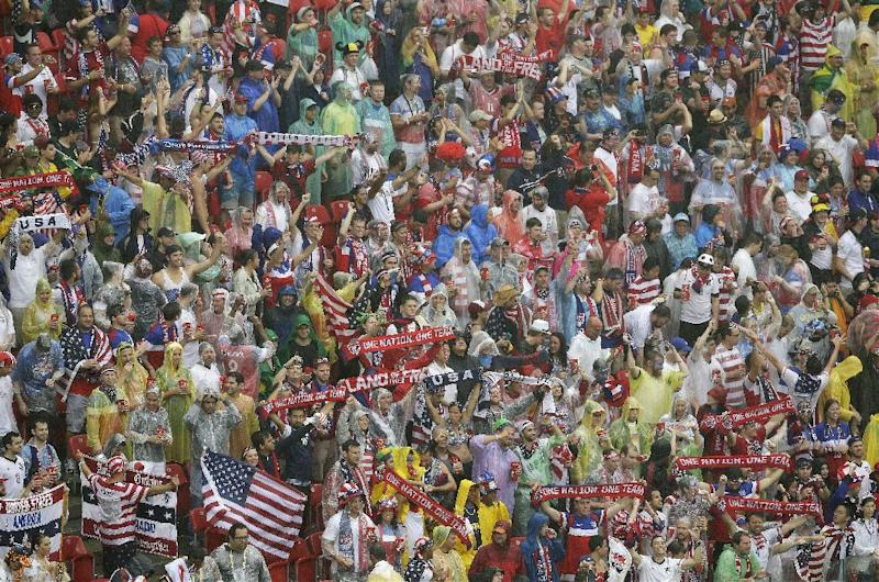 American fans cheer in the rain before the group G World Cup soccer match between the USA and Germany at the Arena Pernambuco in Recife, Brazil, Thursday, June 26, 2014