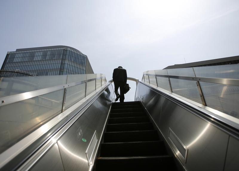 A businessman rides on an escalator in Tokyo's business district