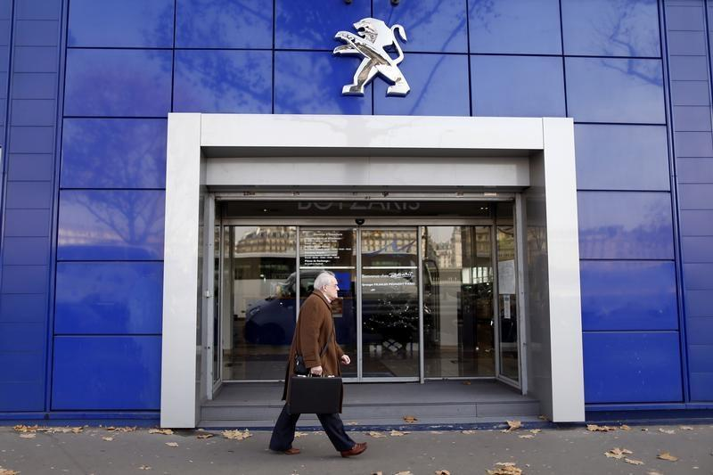 A man walks in front of a Peugeot automobile dealership in Paris