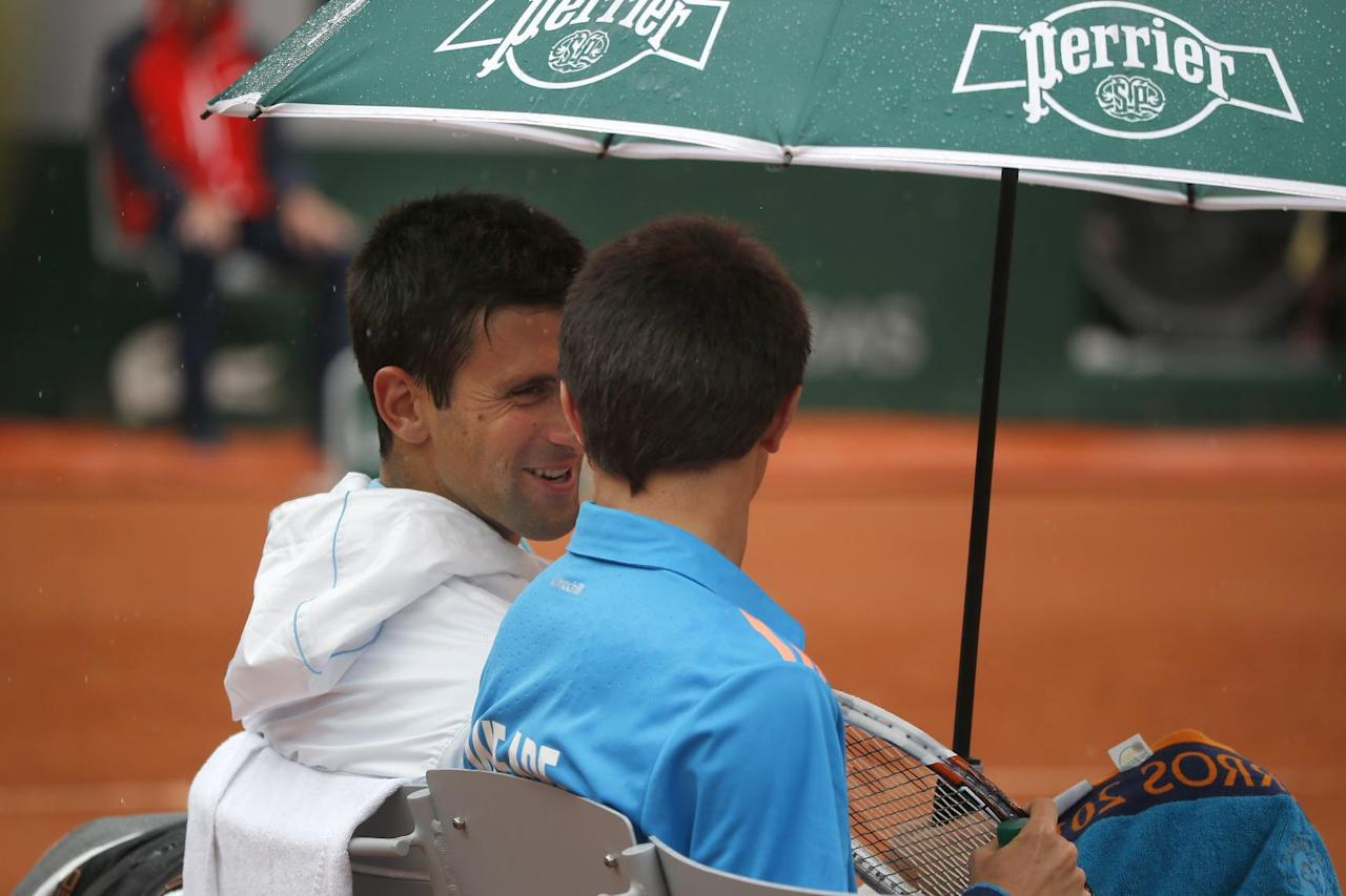 Serbia's Novak Djokovic, left, talks to a ball boy after inviting him to sit on his bench during a break during the first round match of the French Open tennis tournament against Portugal's Joao Sousa at the Roland Garros stadium, in Paris, France, Monday, May 26, 2014. (AP Photo/Michel Euler)