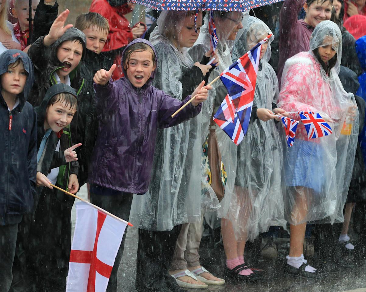 This photo made available by LOCOG shows school children waiting in the rain for the Olympic Torch Relay to arrive in Mansfield, England on Day 41 of the London 2012 Olympic Torch Relay Thursday June 28, 2012. (AP Photo/Gareth Fuller/LOCOG, HO) The Torchbearer's name is provided in good faith, however the Press Association has been unable to verify it independently.