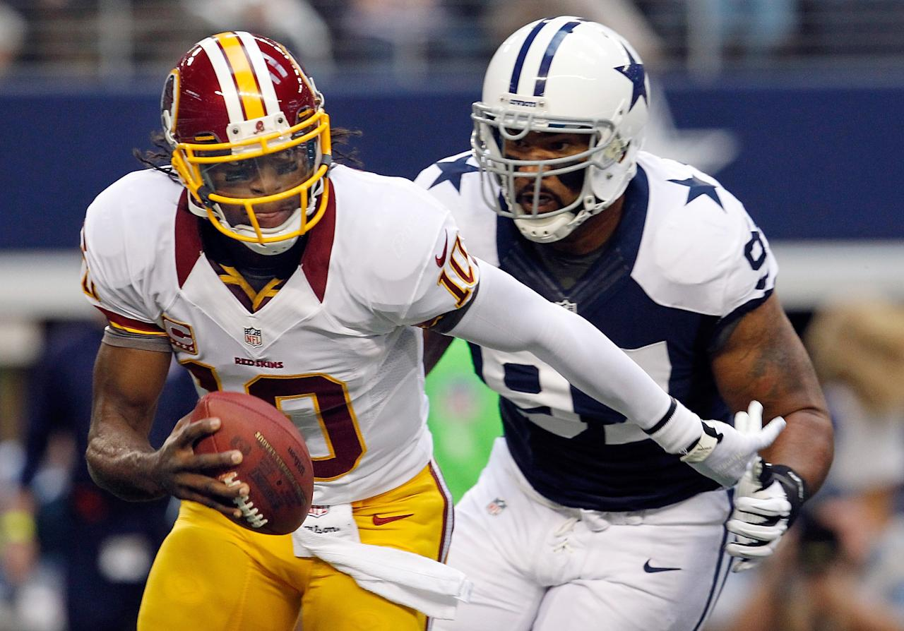 ARLINGTON, TX - NOVEMBER 22:  Robert Griffin III #10 of the Washington Redskins scrambles with the ball before being sacked by Jason Hatcher #97 of the Dallas Cowboys on Thanksgiving Day at Cowboys Stadium on November 22, 2012 in Arlington, Texas.  (Photo by Tom Pennington/Getty Images)