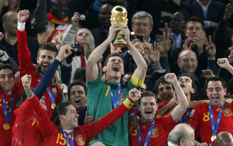 "FILE _ This is a file photo of  Spain's goalkeeper Iker Casillas, center, as he holds up the World Cup trophy with team members as they celebrate their victory at the end of the World Cup final soccer match between the Netherlands and Spain at Soccer City in Johannesburg, South Africa. Winning the soccer World Cup can bring instant rewards to that country's stock market investors. But they better be quick as the post-victory rally doesn't last long.  That's the conclusion of investment bank Goldman Sachs, which published a wide-ranging report late Tuesday  May 27, 2014 on the World Cup and its economic impact. Goldman Sachs analysts found ""a clear pattern of out performance by the wining team in the weeks after the World Cup final."" On average, the investment bank's portfolio strategy team the victor outperforms the global market by 3.5 percent in the first month"
