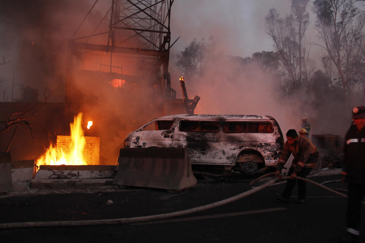 Firefighters work as a house burns after a gas tanker truck exploded on a highway in the Mexico City suburb of Ecatepec, early Tuesday, May 7, 2013. The blast killed and injured dozens, according to the Citizen Safety Department of Mexico State. Officials did not rule out the possibility the death toll could rise as emergency workers continued sifting through the charred remains of vehicles and homes built near the highway on the northern edge of the metropolis. (AP Photo/Gabriela Sanchez)