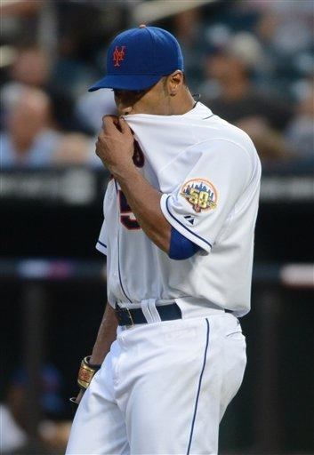 New York Mets' Johan Santana wipes his face in the second inning of the baseball game against the Atlanta Braves at Citi Field in New York, Saturday, Aug. 11, 2012.  Santana gave up eight hits and eight earned runs in his first start since July 20. (AP Photos/Henny Ray Abrams)