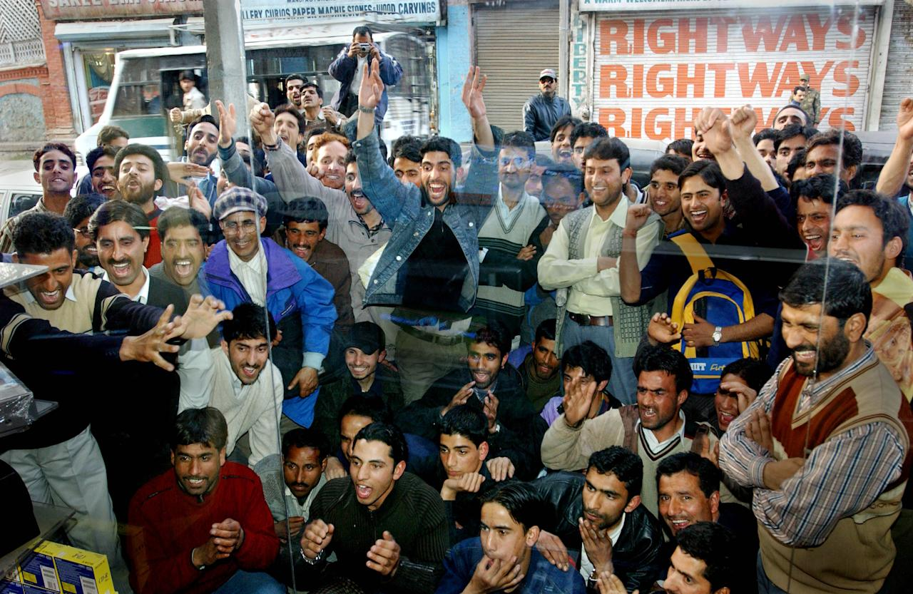 SRINAGAR, KASHMIR, INDIA - MARCH 13: Kashmiri men cheer on the Pakistan team during the nail-biting finale of the cricket match between India and Pakistan in the first one-day international cricket match held in Karachi, Pakistan, March 13, 2004 at their camp in Srinagar, India. This is the first cricket tour held in Pakistan between the two nations in 14 years.  (Photo by Ami Vitale/Getty Images)