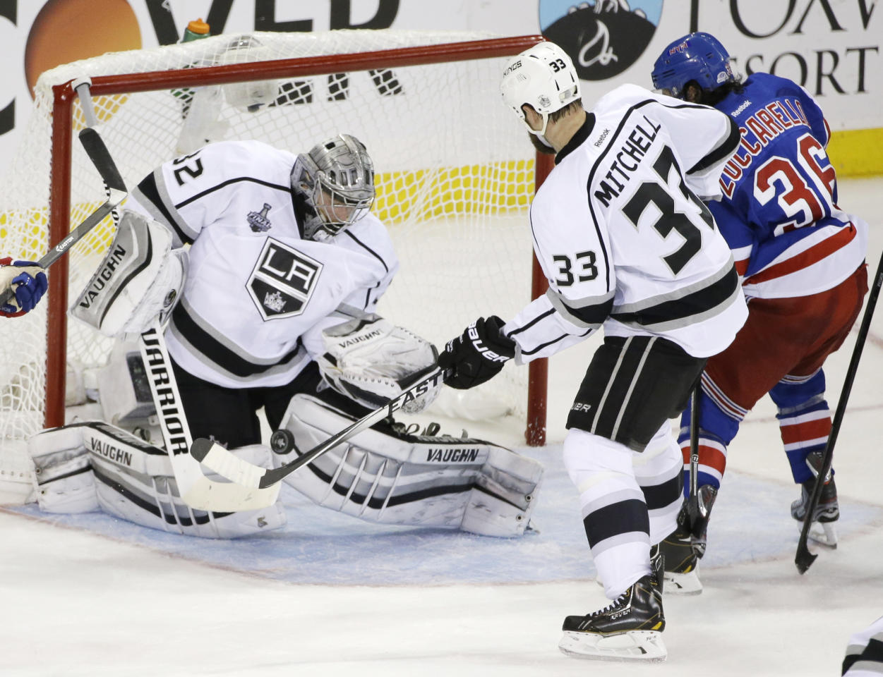 Los Angeles Kings goalie Jonathan Quick (32) blocks a shot by New York Rangers right wing Mats Zuccarello (36) as Kings defenseman Willie Mitchell (33) helps defend in the second period during Game 3 of the NHL hockey Stanley Cup Final, Monday, June 9, 2014, in New York. (AP Photo/Frank Franklin II)