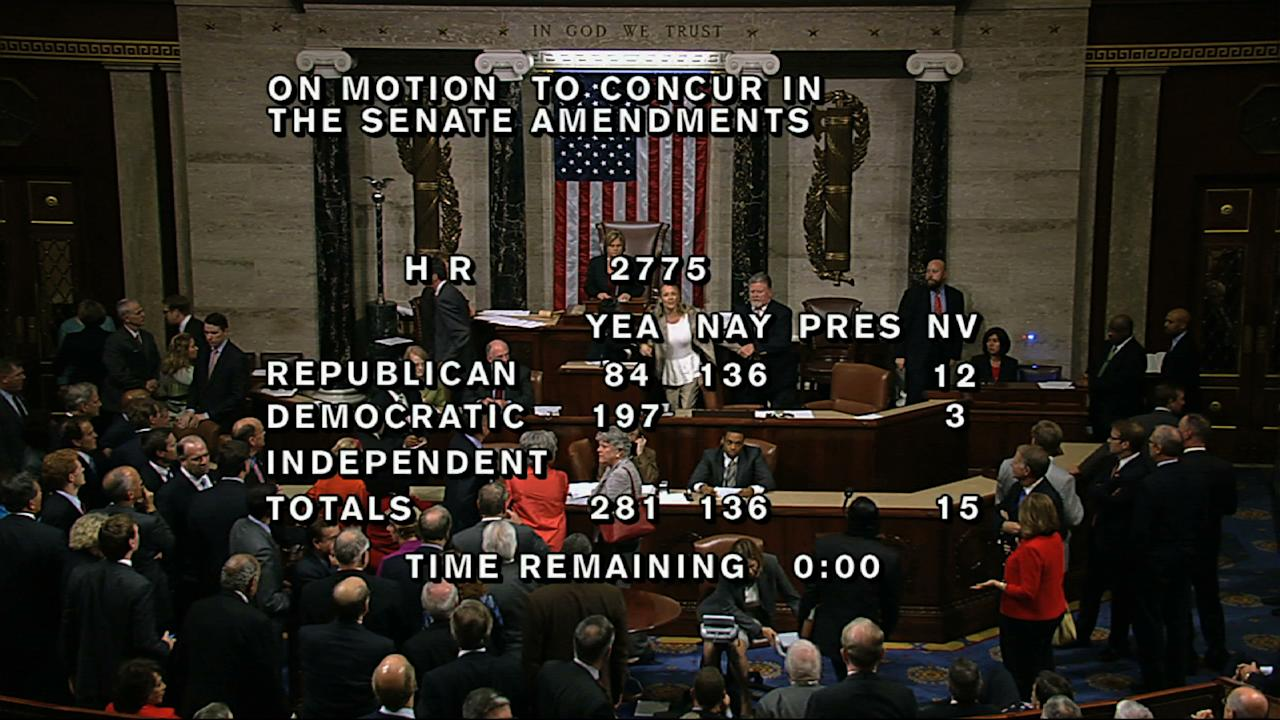 "In this image from House Television, with partial voting totals on the screen, a woman, at the rostrum just below the House presiding officer, seen between the ""yea"" and ""nay"" wording, is removed from the House chamber after she began shouting during the vote for the bill to end the partial 16-day government shutdown and to fund the government. The woman was described by lawmakers and aides as a long-time House stenographer. (AP Photo/House TV)"