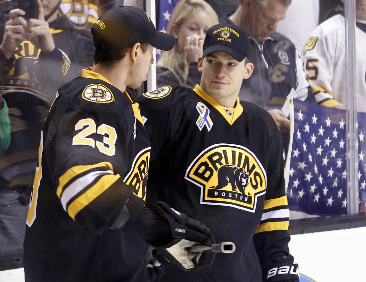 Wearing hats from local law enforcement agencies, Boston Bruins defenseman Andrew Ference, right, talks with teammate Chris Kelly (23) before an NHL hockey game against the Pittsburgh Penguins, Saturday, April 20, 2013, in Boston. (AP Photo/Mary Schwalm)