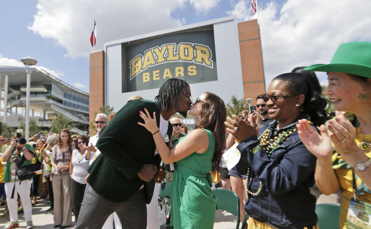 Washington Redskins quarterback Robert Griffin III, left, kisses his wife Rebecca before the dedication of a statute outside the new McLane Stadium before an NCAA college football game between SMU and Baylor Sunday, Aug. 31, 2014, in Waco, Texas. Griffin won the Heisman Trophy when he played at Baylor. (AP Photo/LM Otero)