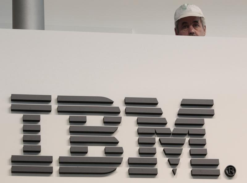A worker is pictured behind a logo at the IBM stand on the CeBIT computer fair in Hanover