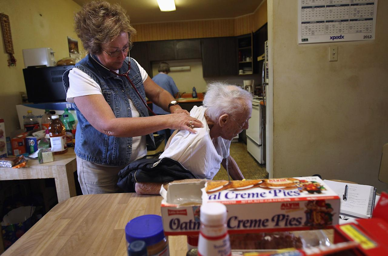 LAKEWOOD, CO - MARCH 26:  Registered nurse Susan Eager (L), checks the breathing of patient Justin Verhoeff, 82, during a house call on March 26, 2012 in Lakewood, Colorado. The Supreme Court Monday began hearing three days of arguments over the 2010 health care overhaul, expected to affect the entire U.S. health industry. Eager works for the Dominican Sisters Home Health Agency, a non-profit that performs thousands of home visits free of charge each year to low-income patients. The agency is funded by private donations and grants and says it helps keep patients, mostly seniors, living in their homes longer, saving federal programs like Medicare millions of dollars each year. (Photo by John Moore/Getty Images)
