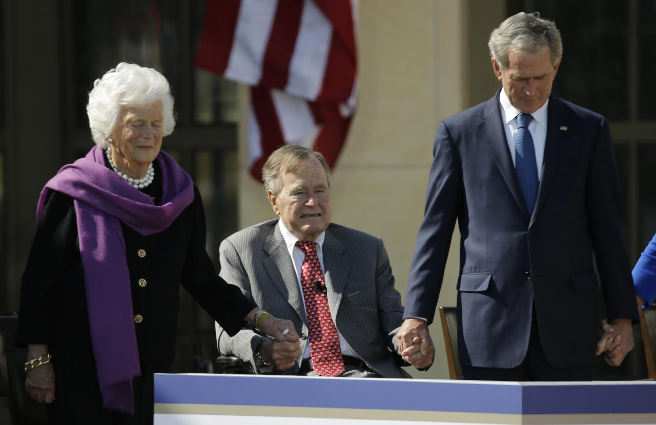 From left, former first lady Barbara Bush, President George H.W. Bush and former president George W. Bush hold hands during the invocation during the dedication of the George W. Bush Presidential Center Thursday, April 25, 2013, in Dallas. (AP Photo/David J. Phillip)
