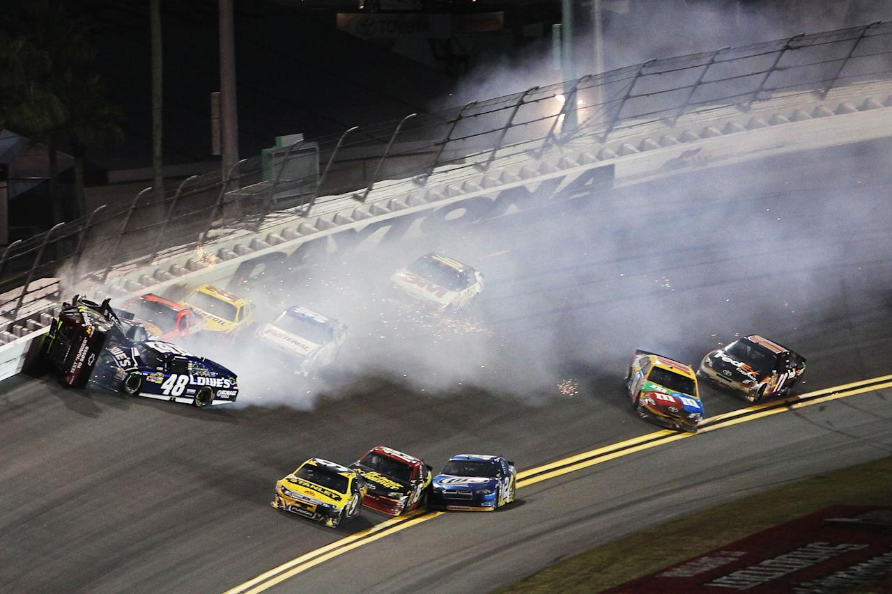 DAYTONA BEACH, FL - FEBRUARY 18:  Jeff Gordon, driver of the #24 Drive to End Hunger Chevrolet, and Kurt Busch, driver of the #51 Tag Heuer Avant-Garde Chevrolet Chevrolet, and Jimmie Johnson, driver of the #48 Lowe's Chevrolet, crash in front of the pack during the NASCAR Budweiser Shootout at Daytona International Speedway on February 18, 2012 in Daytona Beach, Florida.  (Photo by Jamie Squire/Getty Images)