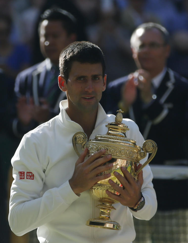 Novak Djokovic of Serbia holds the trophy after defeating Roger Federer of Switzerland in the men's singles final at the All England Lawn Tennis Championships in Wimbledon, London, Sunday July 6, 2014. (AP Photo/Pavel Golovkin)